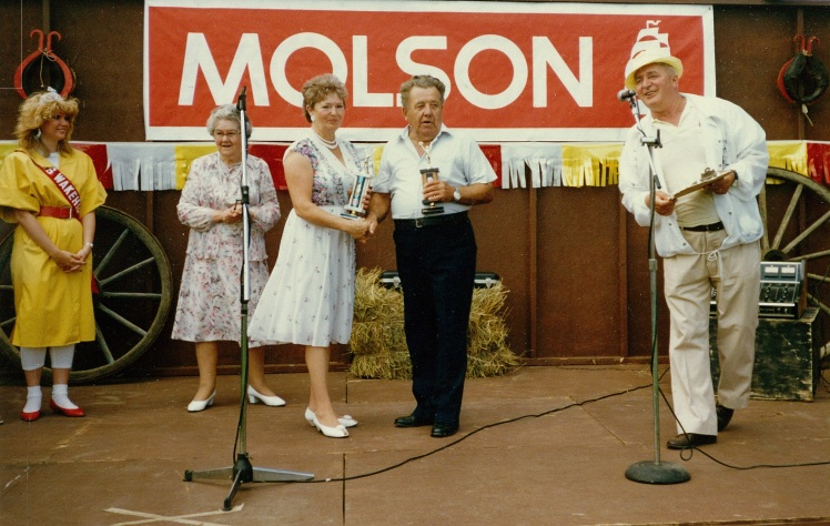 Erskine Morris receives the 2nd Place trophy from MaryEllen Drody-Savidant at the fiddlers contest, Wakeham-York Homecoming Festival 1979. (Photo courtesy of Albert Patterson)
